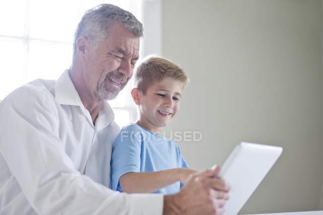 Großvater und Enkel mit digital-Tablette drinnen und lächelnd — Stockfoto