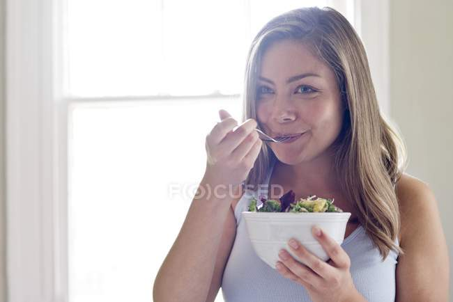 Woman eating bowl of vegetable salad — Stock Photo