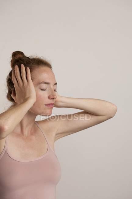 Mulher virou-se para o lado com os olhos fechados, cobrindo as orelhas. — Fotografia de Stock