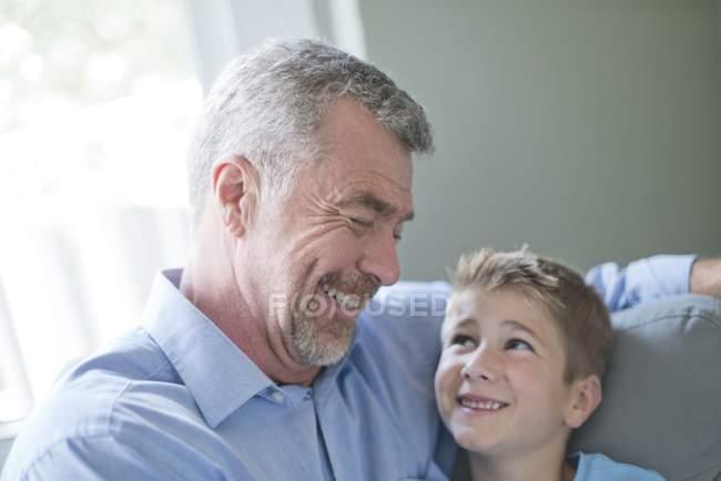 Großvater und Enkel sitzen sich gegenüber und lächeln. — Stockfoto