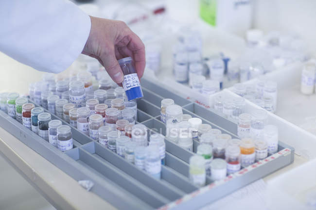Chemist hand picking samples stored in crimp neck vials in pharmaceutical laboratory. — Stock Photo
