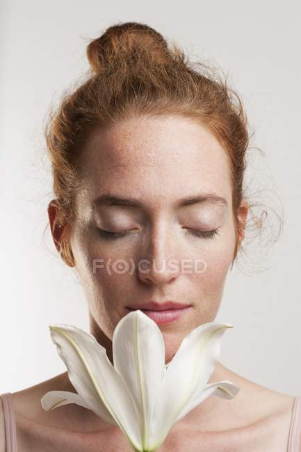 Woman with eyes closed smelling white flower. — Stock Photo