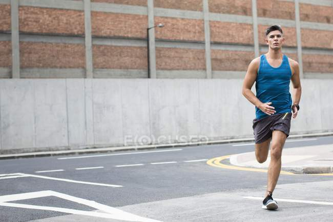Man in sportswear running on road. — Stock Photo