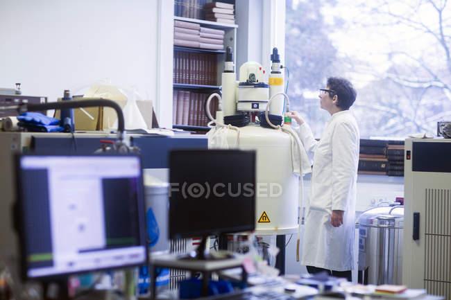 Chimiste utilisant un spectromètre à résonance magnétique nucléaire en laboratoire pharmaceutique . — Photo de stock