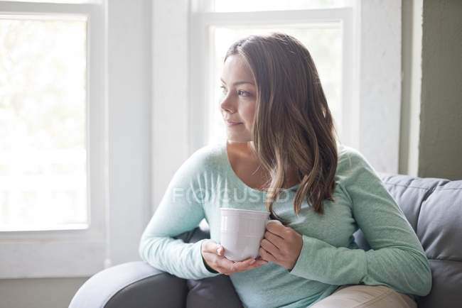 Young woman holding mug and looking away. — Stock Photo