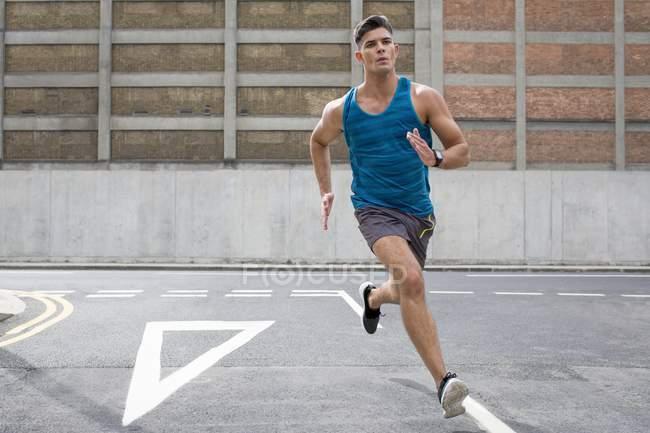 Мужчина в спортивной одежде бежит по дороге . — стоковое фото