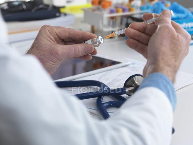 Doctor filling syringe for injection. — Stock Photo