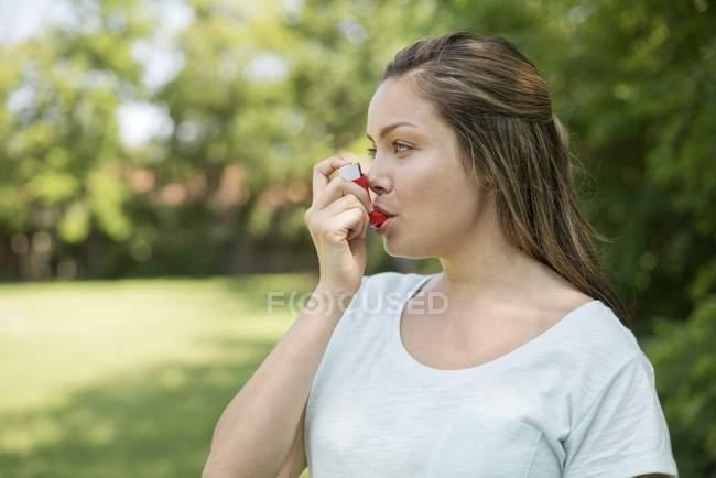 Mulher jovem usando inalador ao ar livre . — Fotografia de Stock