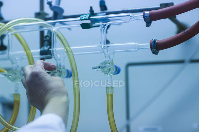 Close-up of hand adjusting tap on burette tube in pharmaceutical laboratory. — Stock Photo