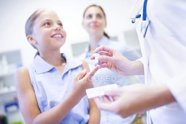 Доктор проверяет молодую девушку на укол пальца. . — стоковое фото
