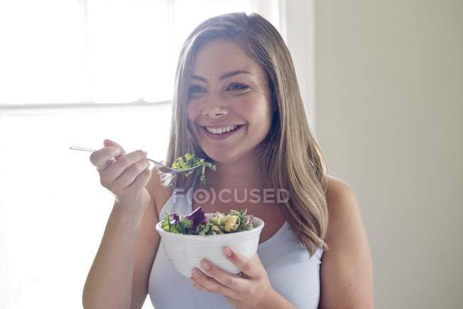 Portrait of young woman eating salad. — Stock Photo