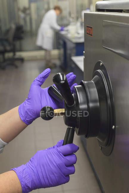 Technician hands opening sterilization tank. — Stock Photo