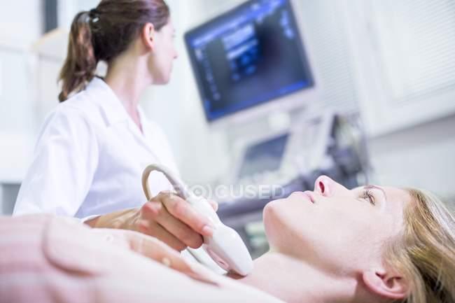 Sonografista realizando ultra-som em paciente do sexo feminino. — Fotografia de Stock