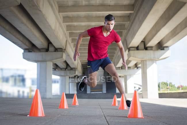 Man running around plastic cones under bridge. — Stock Photo