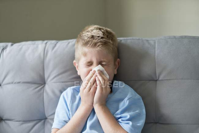 Boy blowing nose on tissue. — Stock Photo