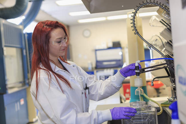 Female chemist working with reagent supply. — Stock Photo