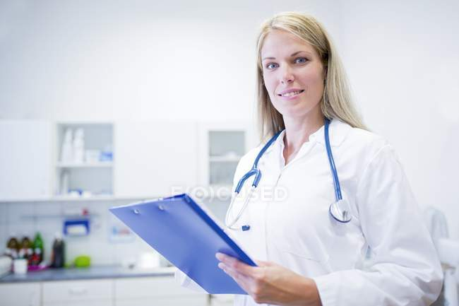 Female doctor standing with clipboard, portrait. — Stock Photo