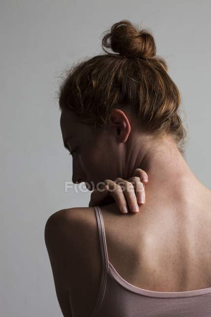 Woman touching neck with hand. — Stock Photo