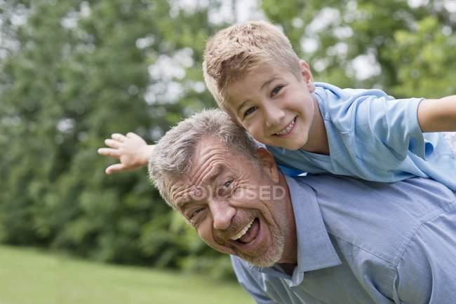 Großvater trägt Enkel auf Schultern mit ausgestreckten Armen, Porträt. — Stockfoto
