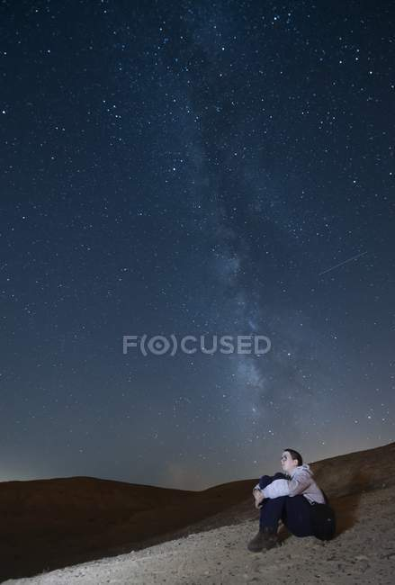 Scenic view of teenager looking up at stars of Milky Way galaxy. — Stock Photo