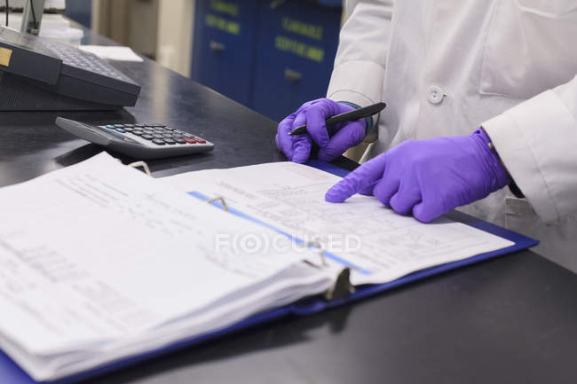 Cropped view of technician hands recording data from test. — Stock Photo