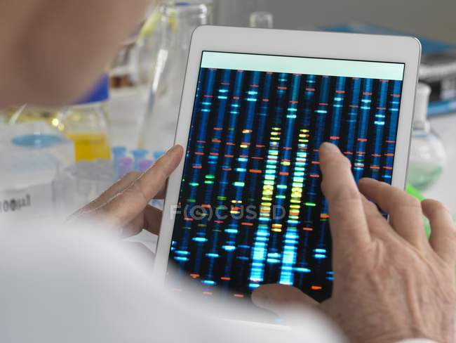 Scientist viewing results of genetic test on digital tablet. — Stock Photo