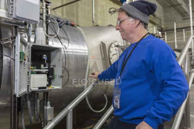 Water department engineer inspecting instrumentation panel. — Stock Photo
