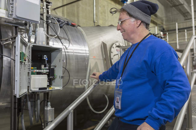 Water department engineer inspecting instrumentation panel. — Stock Photo