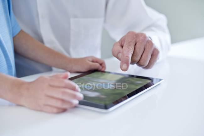 Kind und Senior Mann mit digital-Tablette, close-up — Stockfoto