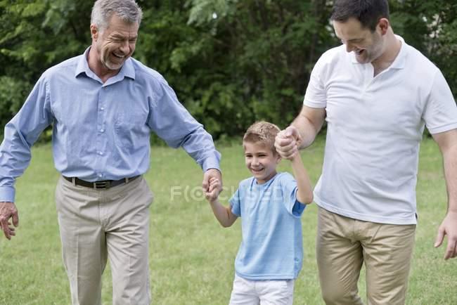 Abuelo, padre y niño cogidos de la mano y sonriendo al aire libre. - foto de stock