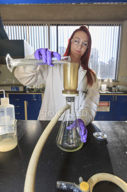 Chemist adding sample to filtration strainer. — Stock Photo