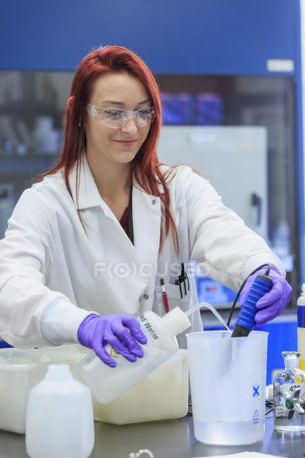 Chemist adding distilled water while measuring pH. — Stock Photo