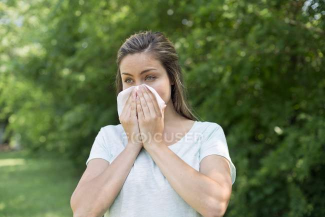 Woman blowing nose on tissue outdoors. — Stock Photo