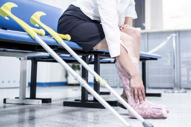 Mujer con pierna en yeso sentada en silla con muletas . - foto de stock