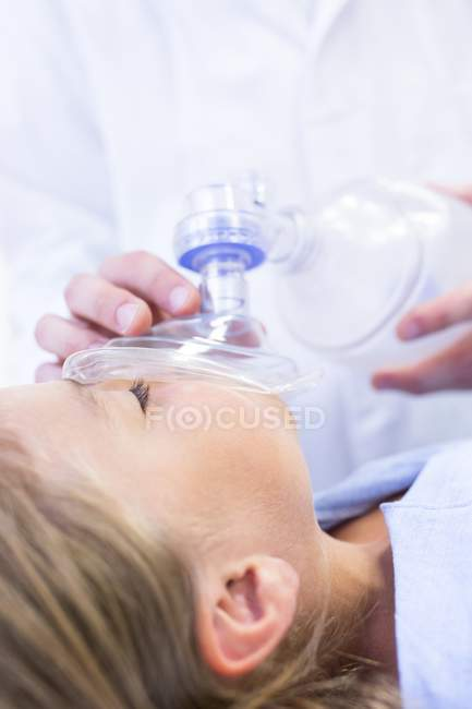 Close-up of hands of male doctor putting anaesthetic mask on girl. — Stock Photo