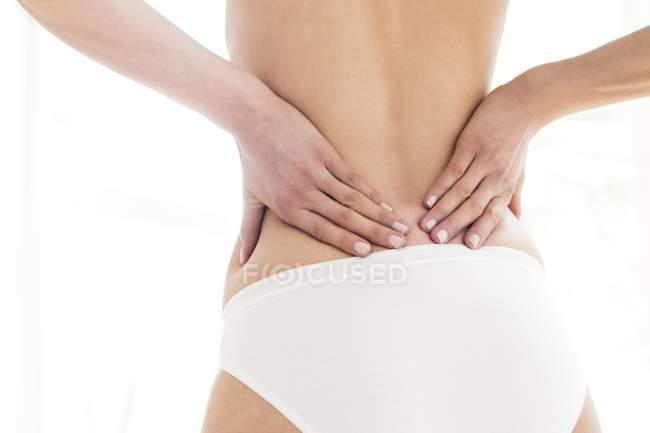 Mujer frotando espalda baja, vista trasera . - foto de stock