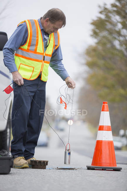Water department technician using flow rate sensor. — Stock Photo