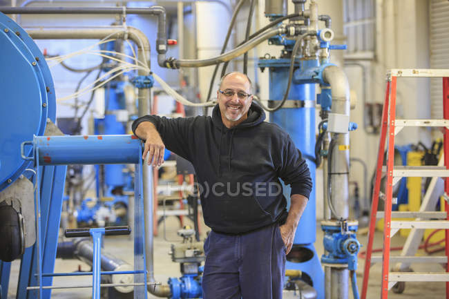 Engineer leaning on equipment at water treatment plant. — Stock Photo