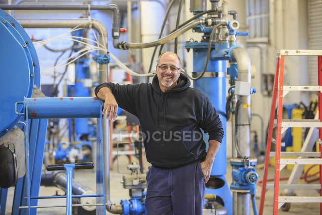 Ingenieur stützt sich auf Ausrüstung in Wasseraufbereitungsanlage. — Stockfoto