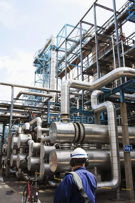 Engineer looking at gas and oil pipes at power plant. — Stock Photo