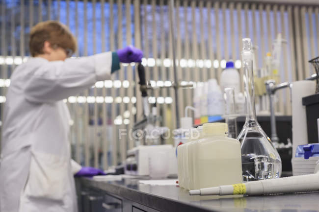Laboratory equipment with female technician adding reagent in background. — Stock Photo