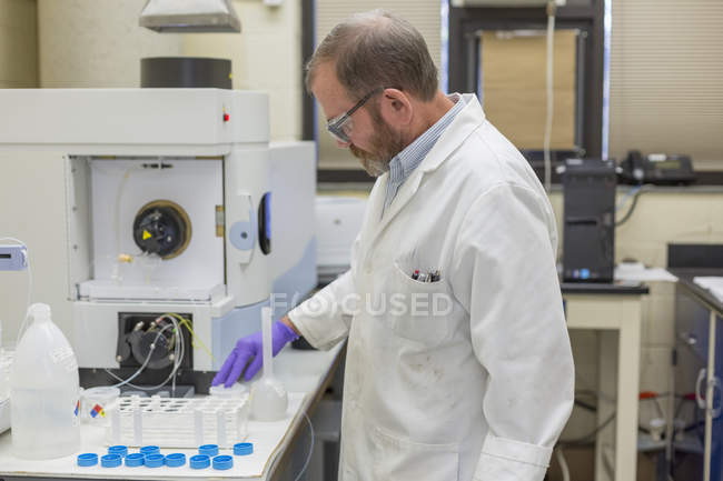 Chemist preparing tubes for automated test. — Stock Photo