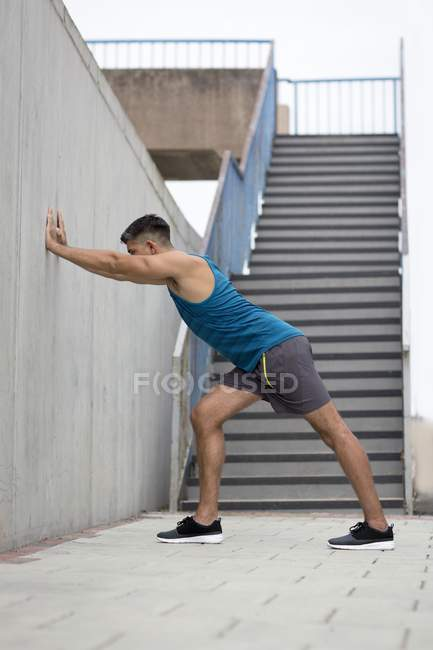 Man leaning on wall and stretching. — Stock Photo