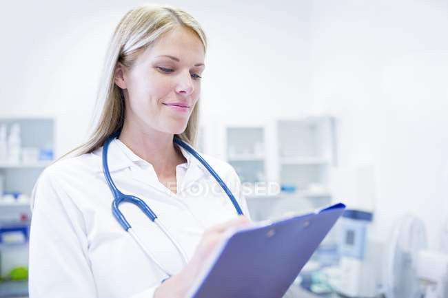 Female doctor standing with clipboard. — Stock Photo