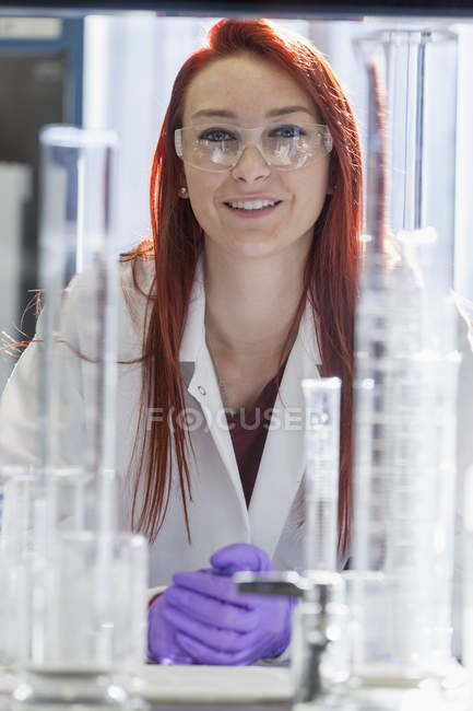 Female chemist at workplace looking in camera. — Stock Photo