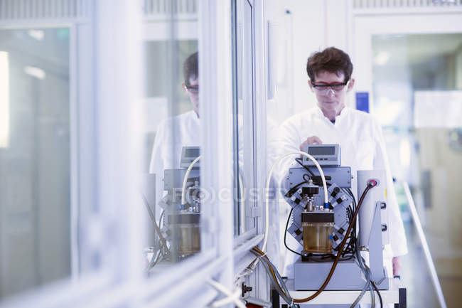 Female chemist setting up equipment in laboratory. — Stock Photo