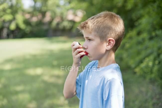 Menino usando inalador ao ar livre . — Fotografia de Stock