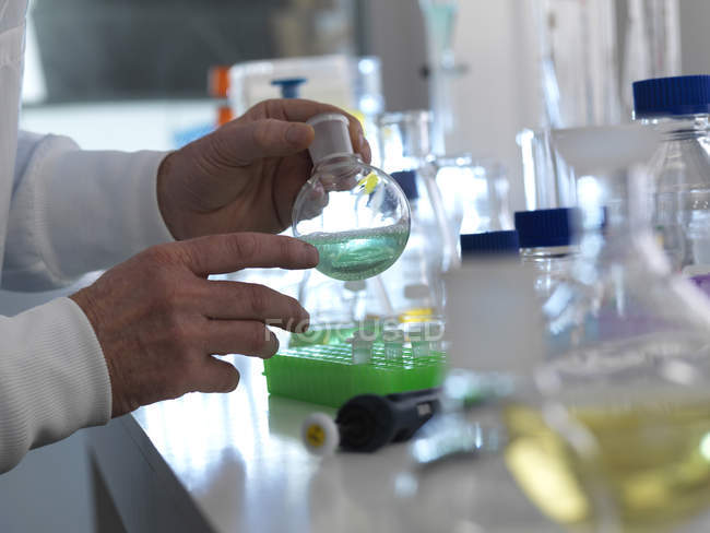 Scientist preparing chemical liquid in laboratory flask. — Stock Photo