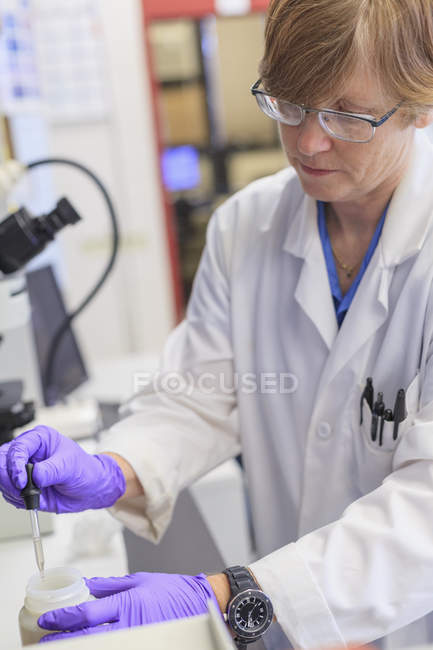 Chemist collecting liquid with dropper. — Stock Photo