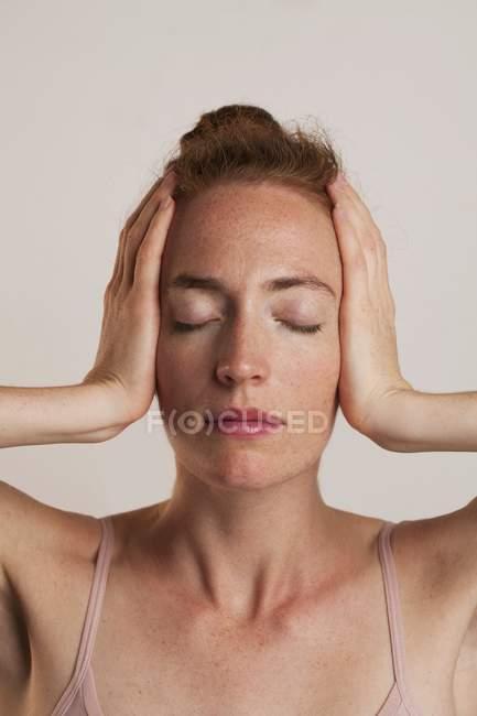 Close-up da mulher cobrindo os ouvidos com os olhos fechados, atirou em estúdio. — Fotografia de Stock